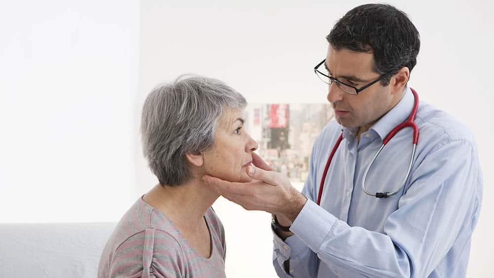 Médico apalpando gânglios do pescoço de uma mulher no consultório.