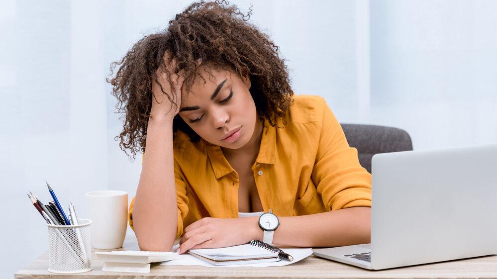 mulher sentada à mesa do escritório, com cabeça sobre a mão em sinal de cansaço por síndrome da fadiga crônica