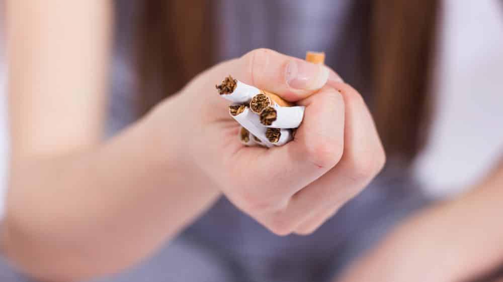 close em mão de mulher amassando cigarros. Parar de fumar envolve cinco fases