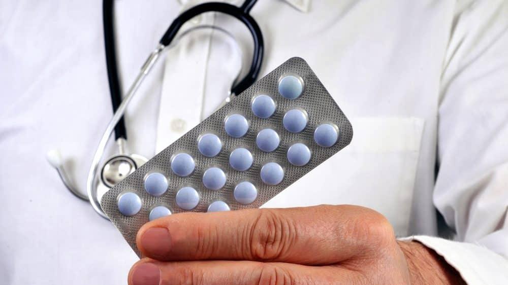 close de mão de médico segurando cartela de medicamentos. remédios para dormir têm efeitos colaterais que podem ser perigosos