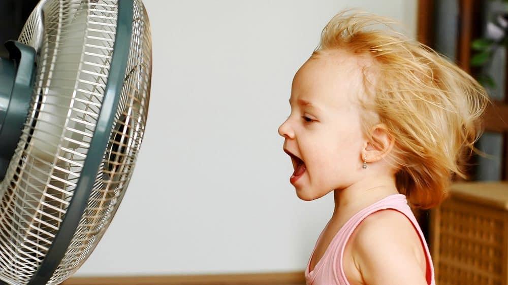 menina em frente ao ventilador. não há relação entre vento e gripe