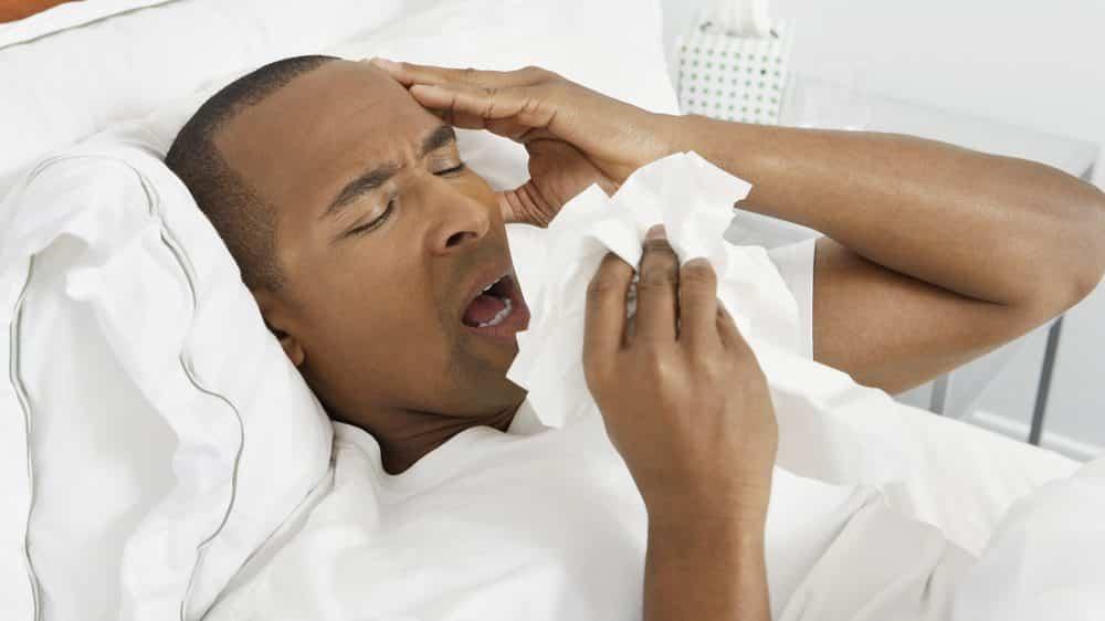homem doente, de cama, espirrando.veja as condições para a propagação da gripe
