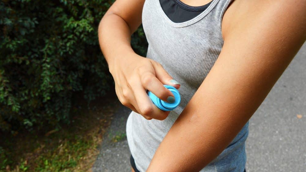 mulher passa repelente no braço. fim da malária ainda está longe