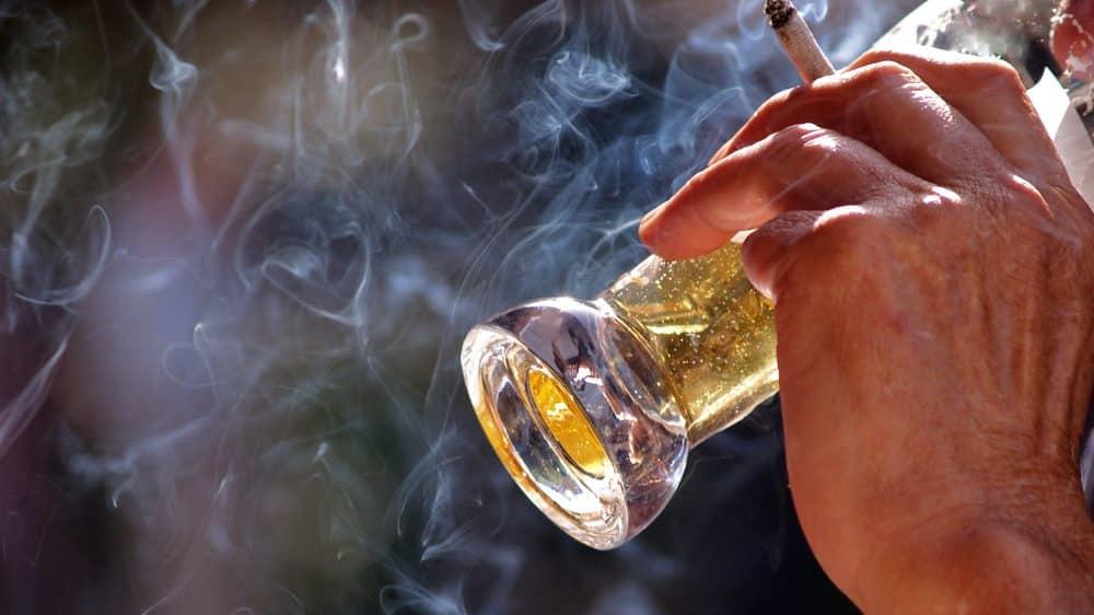homem bebe e fuma em bar. Proibição de fumo em lugares fechados é essencial