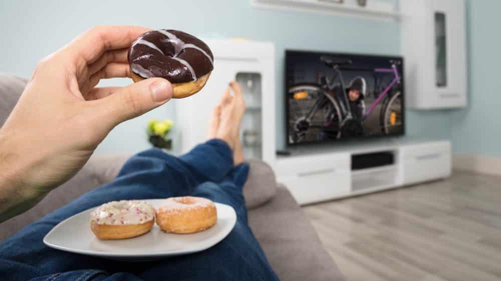 pessoa deitada, comendo donut. veja os mediadores químicos envolvidos na obesidade