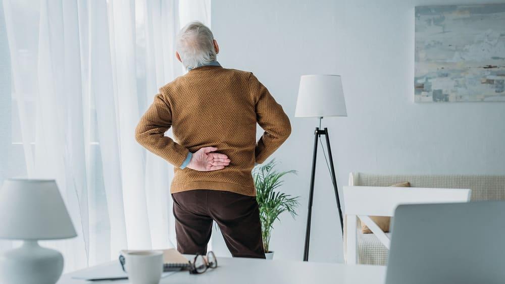 Idoso com dor nas costas, em virtude da hérnia de disco