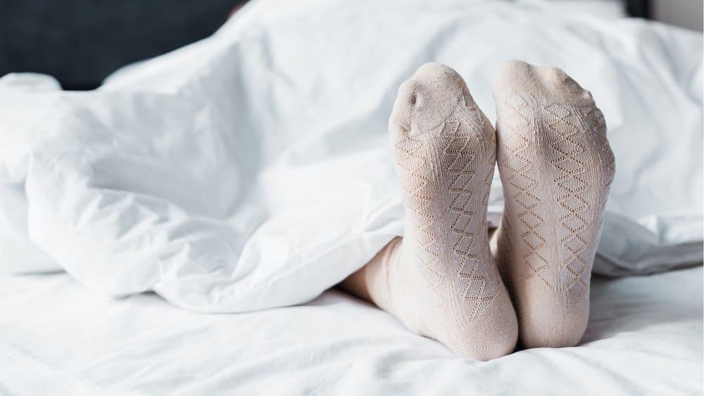 Pessoa deitada numa cama, com somente os pés para fora do lençol