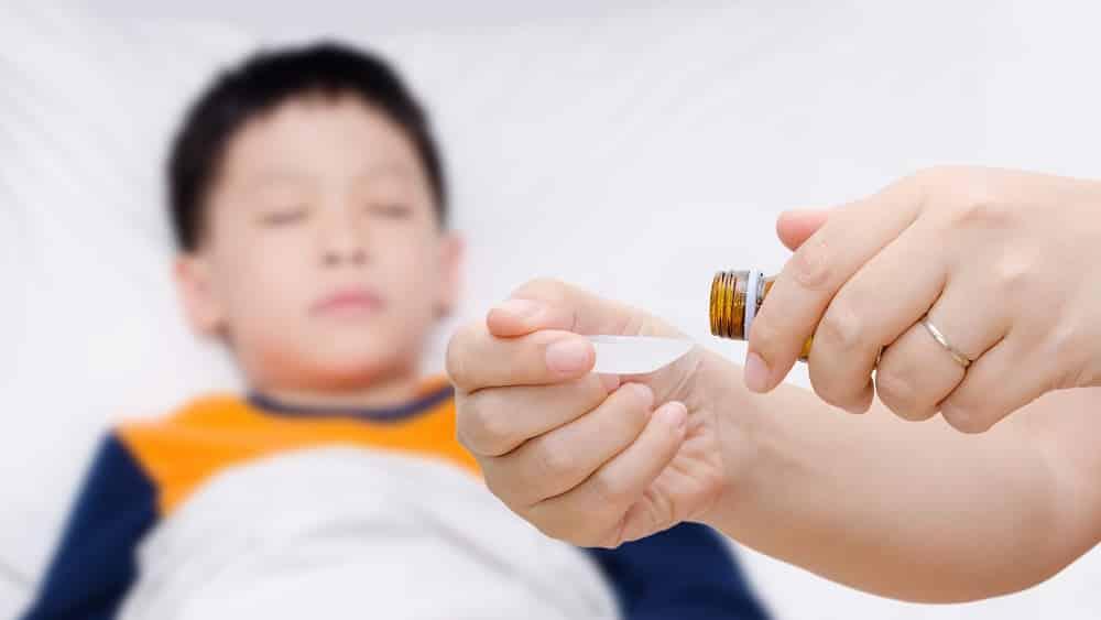 Criança com febre, um dos sintomas da doença de Kawasaki, enquanto a mãe coloca remédio num medidor