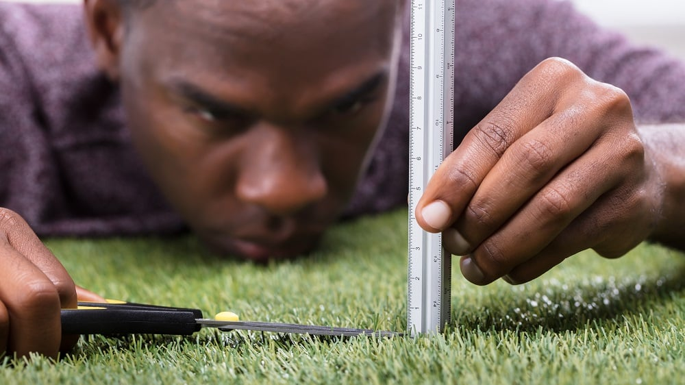 Homem cortando a grama com tesoura e régua, representando o transtorno obsessivo compulsivo (TOC)