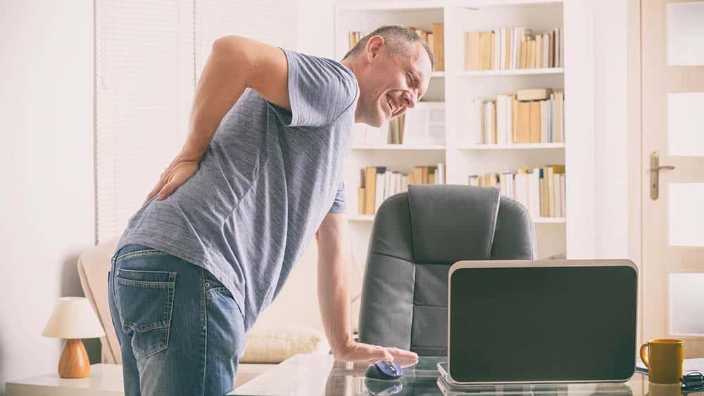 Homem curvado com dor na lombar, um dos sintomas da espondilite anquilosante.