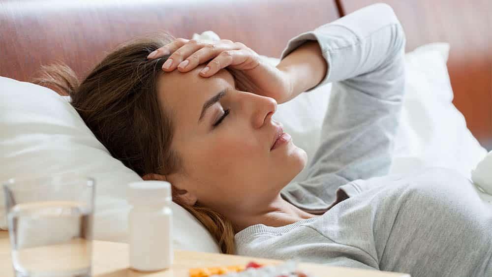 Mulher deitada com mão na testa indicando febre e mal-estar.