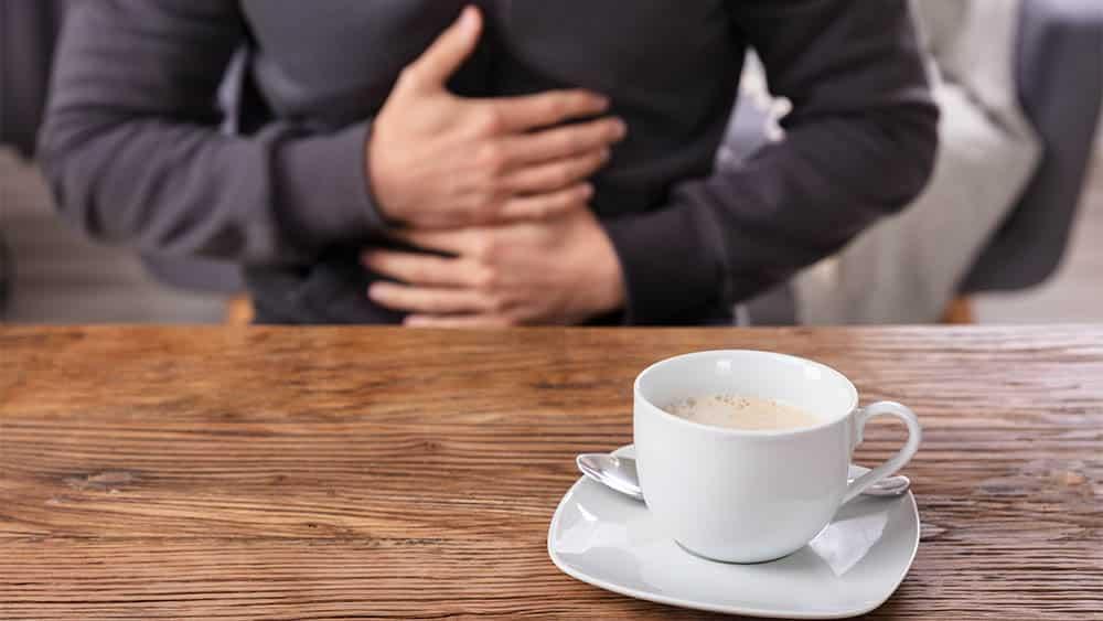 Homem pressionando estômago ao fundo e xícara de café em primeiro plano.