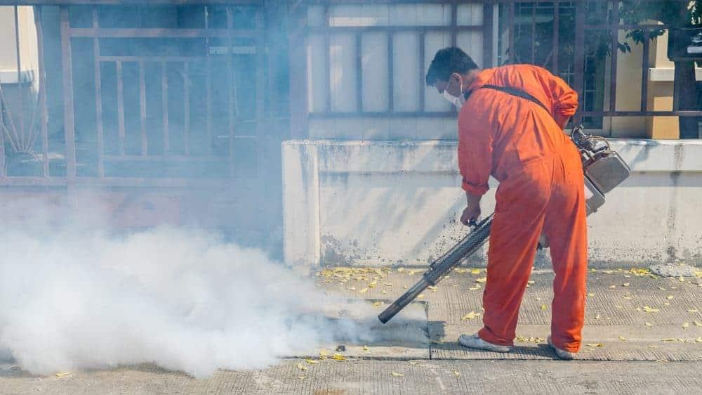 homem faz nebulização em rua para evitar a epidemia de dengue