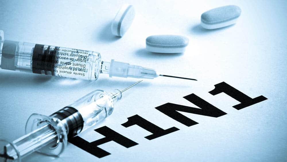 H1N1 escrito em uma folha com comprimidos e seringas sobre ela.