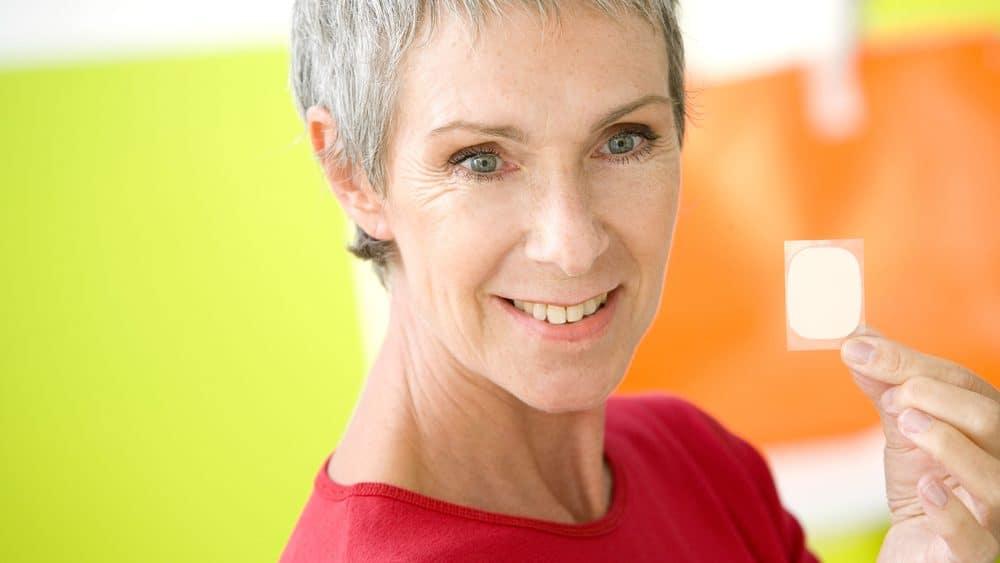 mulher na menopausa segura patch de reposição hormonal