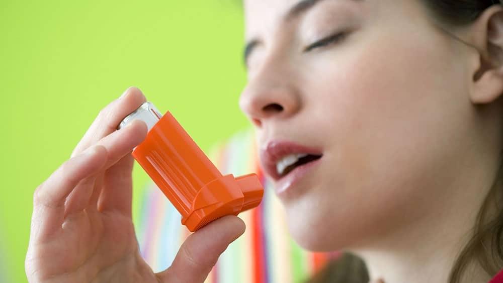 Mulher com bombinha usada para tratamento de crises de asma.