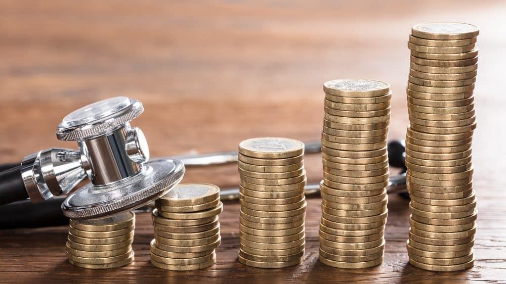 estetoscópio ao lado de moedas empilhadas. Evolução do tratamento de câncer encareceu a medicina