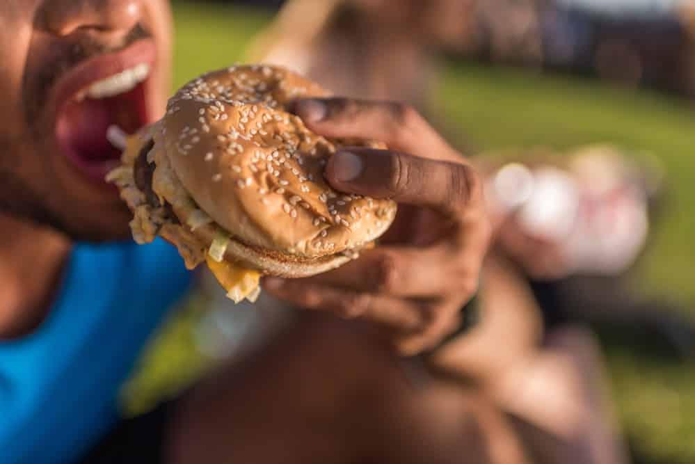 homem dá uma mordida em hambúrguer. Entender os mecanismos envolvidos no controle do apetite pode ajudar a evitar o acúmulo de peso