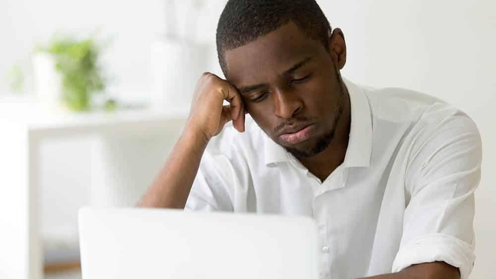 Homem em frente a um notebook com a cabeça apoiada em uma das mãos expressando tédio.
