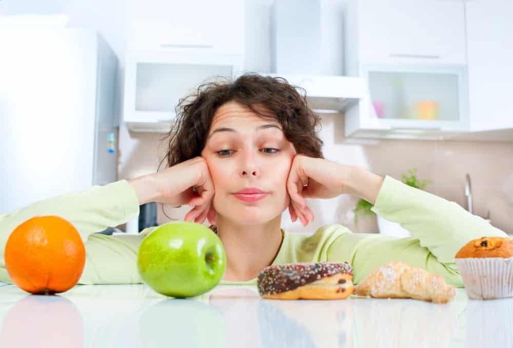 mulher jovem, diante de fruta e doce, fica em dúvida sobre o que comer. Quem tem diabetes deve ingerir pouco açúcar
