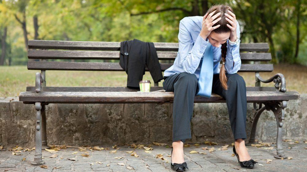 mulher estressada sentada em um banco de praça, com a cabeça entre as mãos