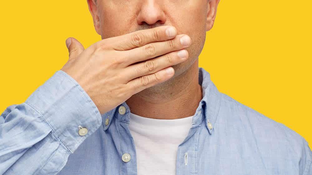 Homem tampando a boca com a mão em típico gesto de cobrir um arroto.