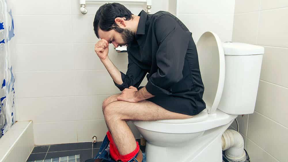 Homem de perfil sentado no vaso sanitário com a mão na cabeça e expressão de dor.