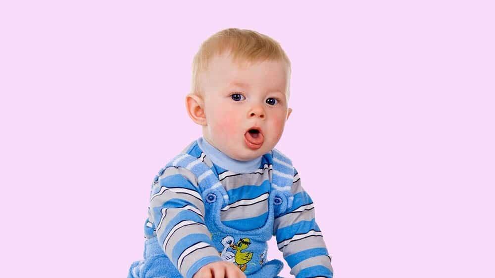Bebê com expressão de tosse, um dos sintomas da bronquiolite.