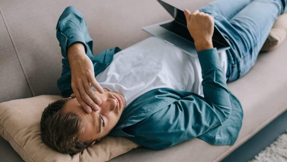 homem deitado no sofá, com computador no colo, sonolento