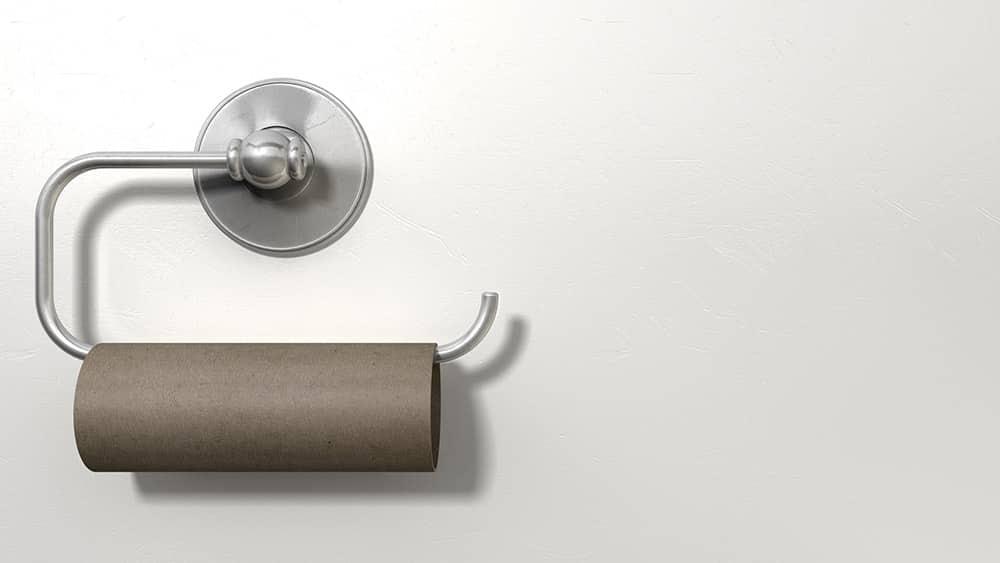 Suporte de papel higiênico preso a uma parede branca com um rolo vazio.