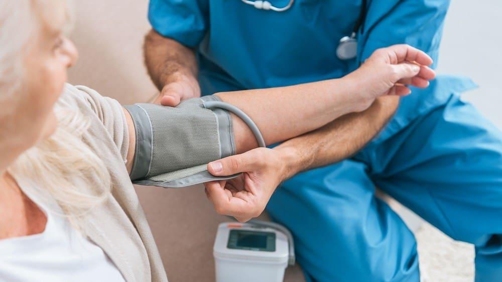 Profissional de saúde medindo a pressão arterial de senhora.
