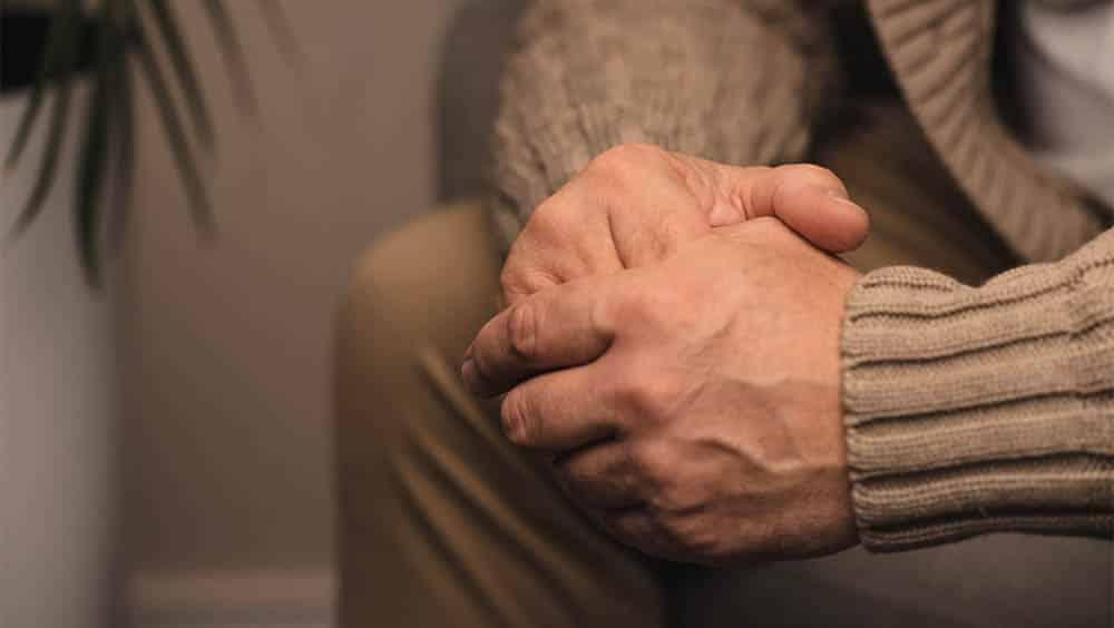 Homem mais velho segurando as próprias mãos.