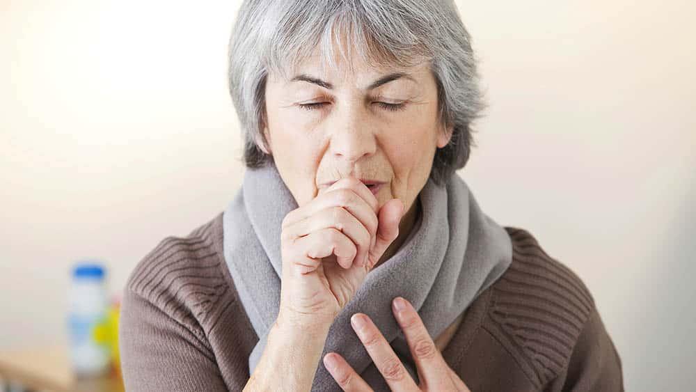 Mulher cobrindo a boca com a mão, em gesto de tosse, um dos principais sintomas da fibrose cística.