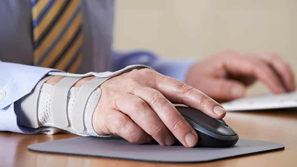 Mão de executivo utilizando uma órtese mexendo em um mouse.