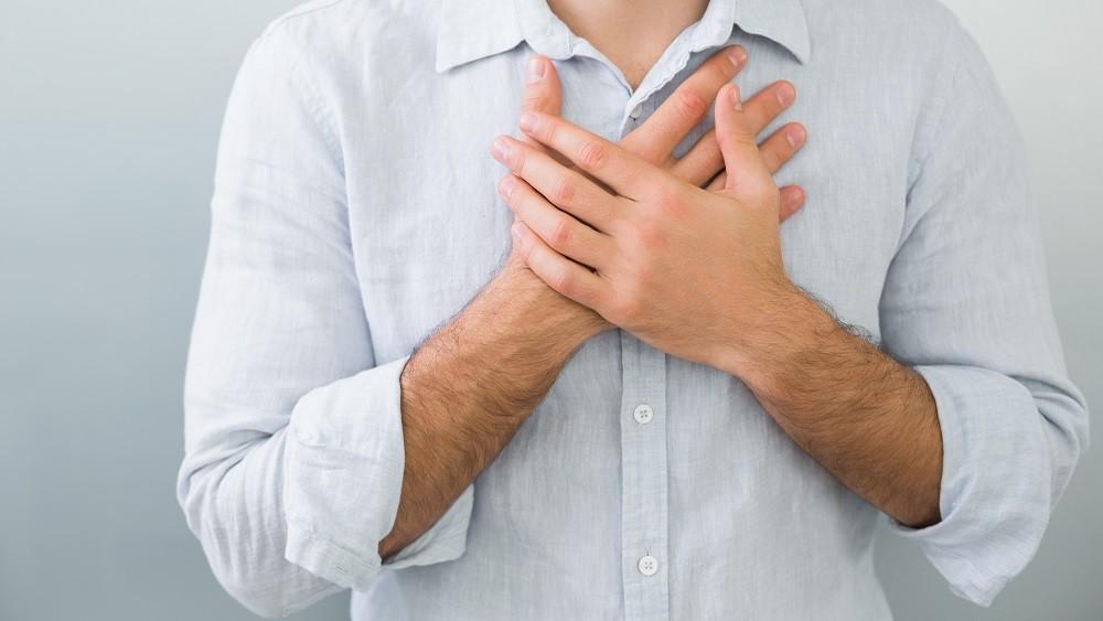 Homem com as mãos no peito.