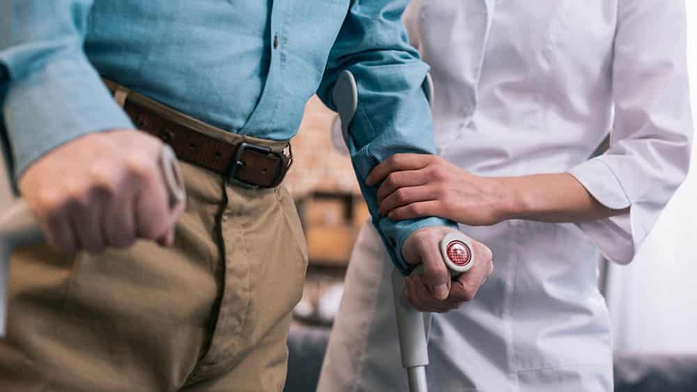 Homem com muletas sendo ajudado a caminhar por profissional de saúde.
