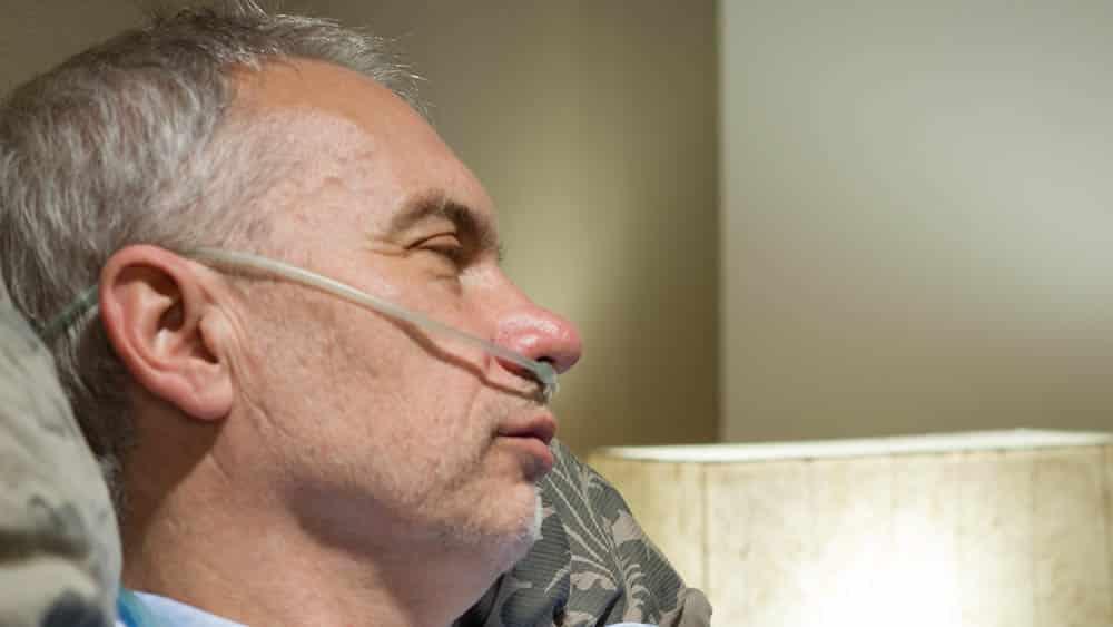 Homem com tubo de oxigênio no nariz, necessário em casos avançados de enfisema.