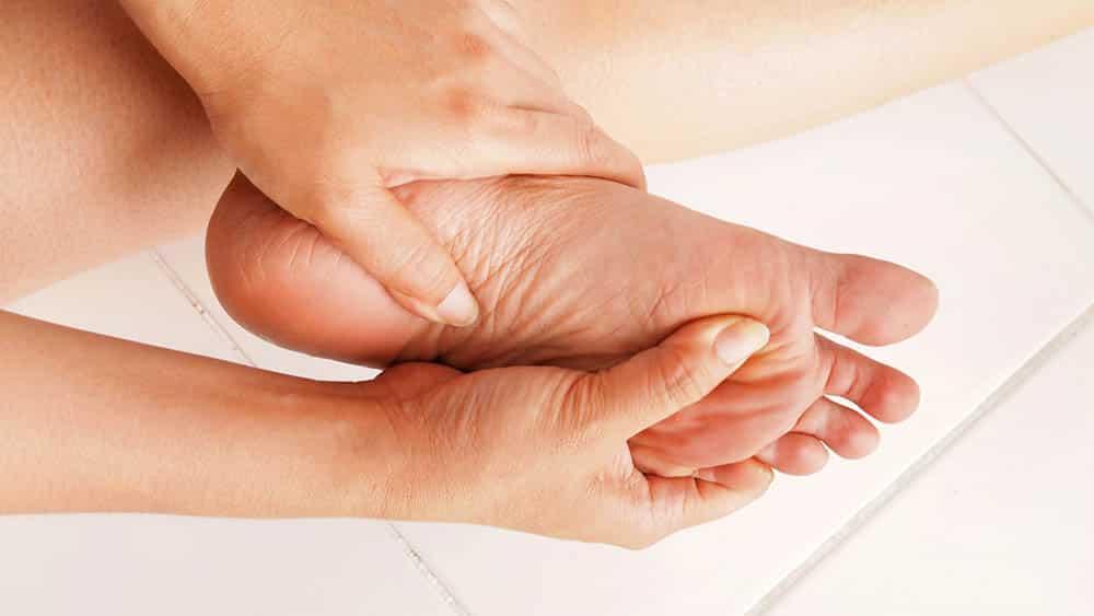 mão de uma mulher segurando o próprio pé, local mais atingido pela frieira.