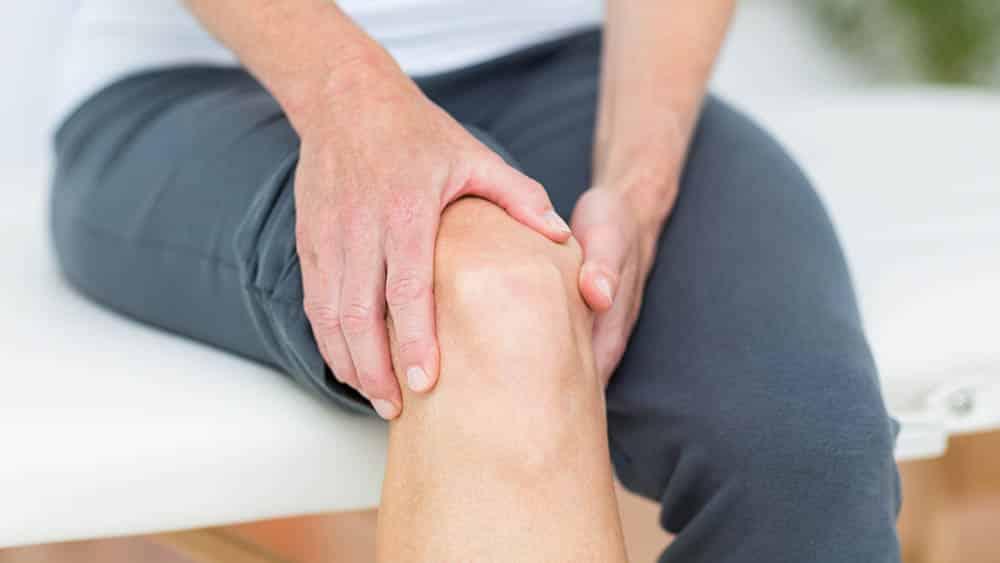 Close em mãos de mulher apalpando o joelho, um dos locais mais atingidos pela bursite.