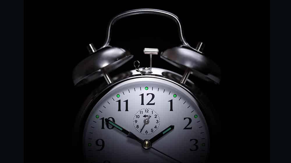 Despertador clássico em uma sala escura, com iluminação mostrando somente sua metade superior.