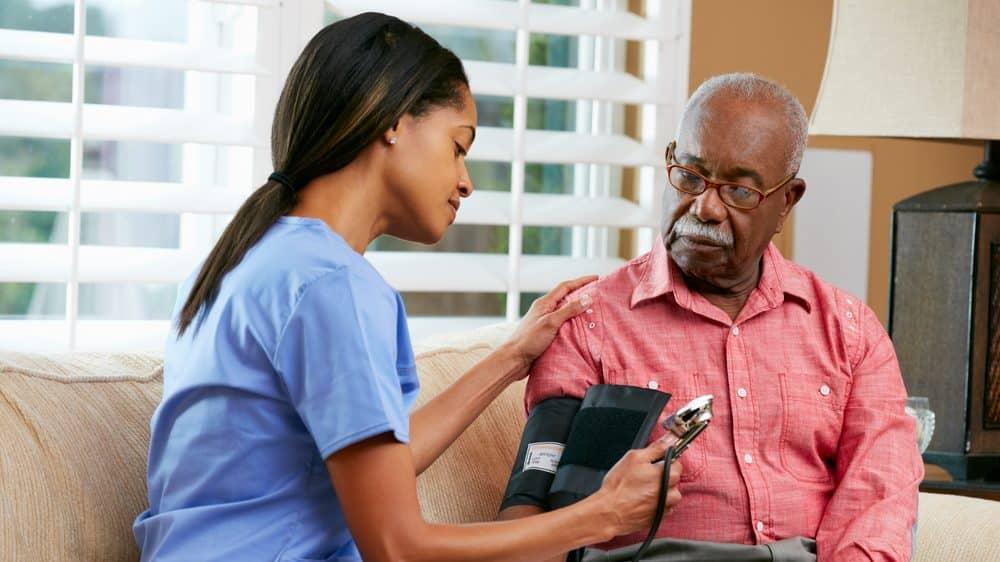 enfermeira mede pressão de homem idoso. tratamento da hipertensão requer mudança de estilo de vida