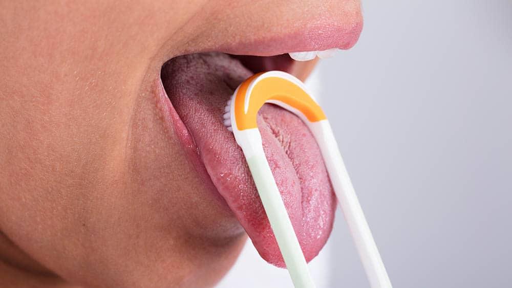 Close em boca de mulher usando raspador de língua.