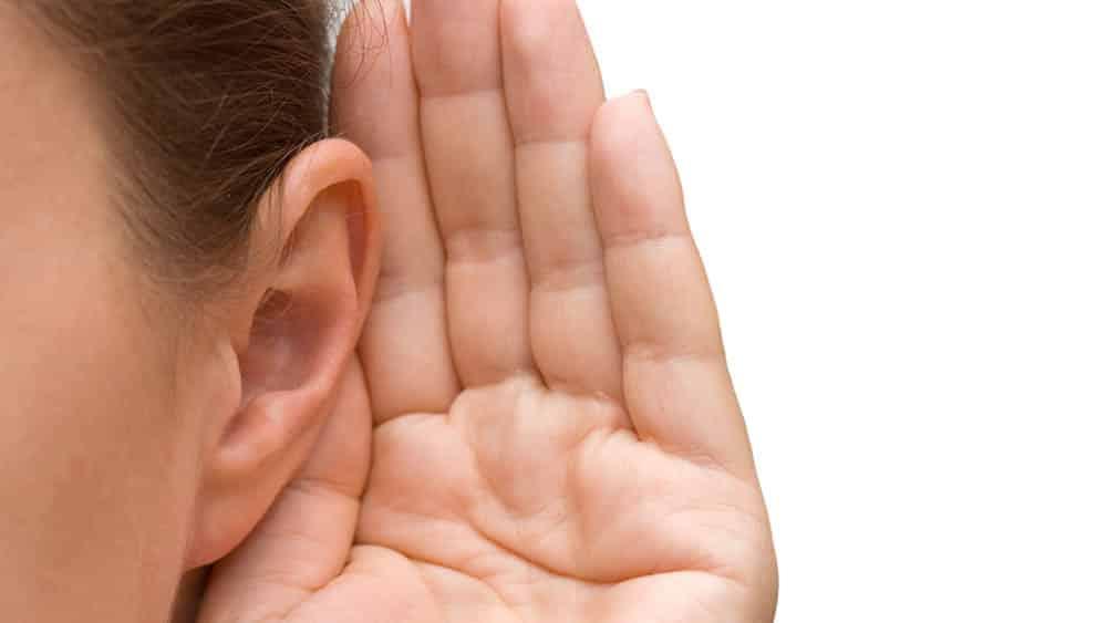 Mulher com mão em concha na orelha.