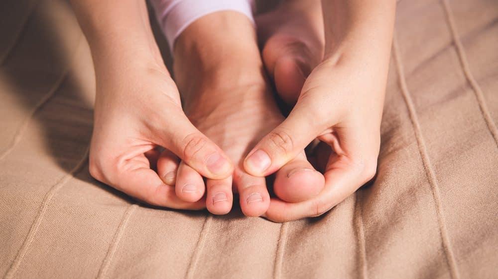 close em pé sendo massageado. gota causa dores fortes na região