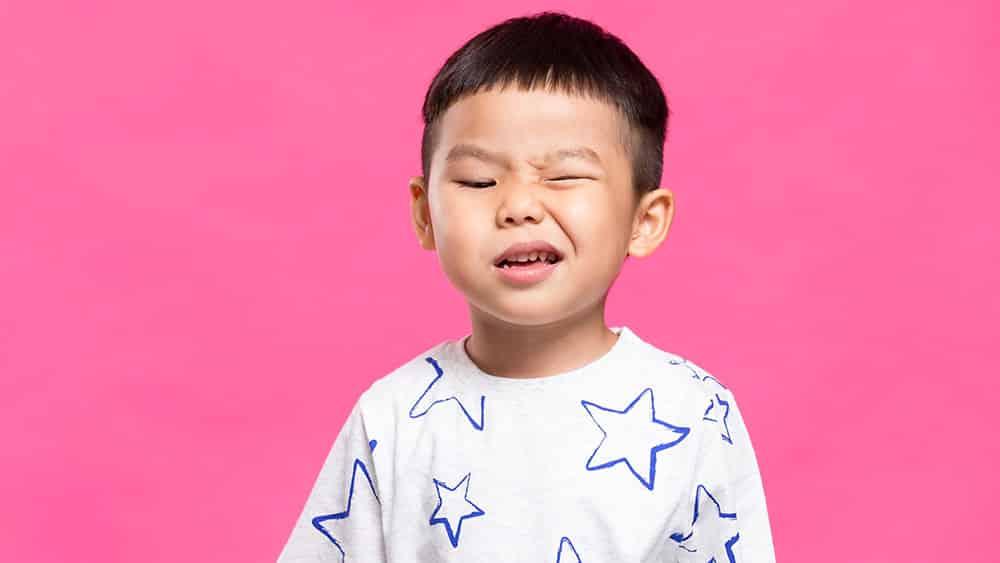 Menino asiático em um fundo rosa piscando um olho.
