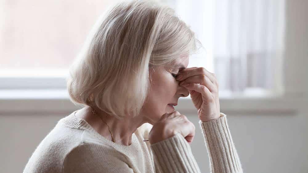Mulher mais velha de perfil com mão apertando entre os olhos indicando tontura.