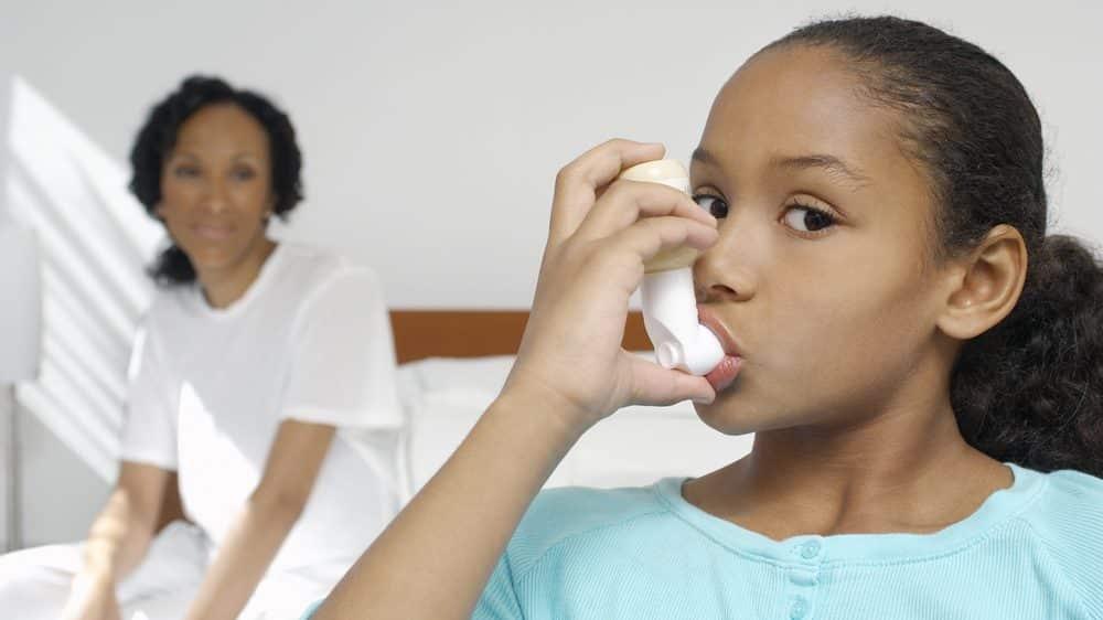 menina com bombinha de asma e mãe ao fundo. Incidência de asma é maior em crianças criadas em ambientes estéreis.