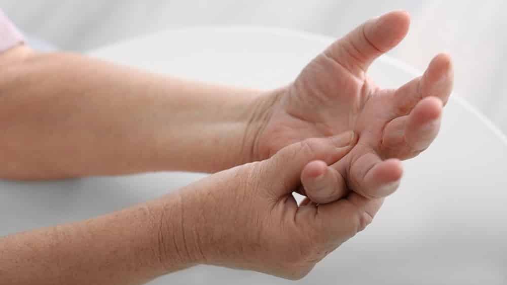 Mulher mais velha pressionando articulação da palma da mão.