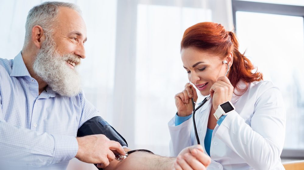 médica afere pressão de paciente com hipertensão