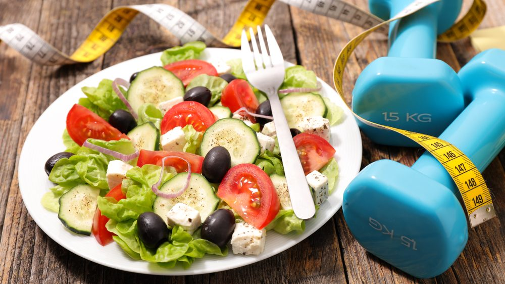 prato de salada, peso e fita métrica sobre a mesa, indicando estilo de vida saudável